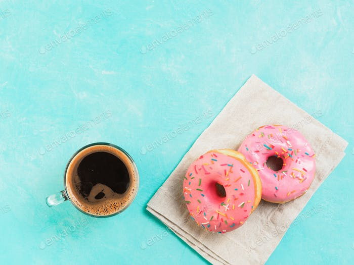 pink donuts and coffee on blue background , copy space, top view