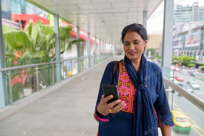 Mature beautiful Indian woman using digital tablet