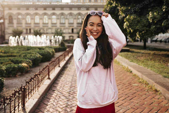 Cool young brunette woman in pink hoodie, red silk skirt smiles sincerely, looks happy and puts off