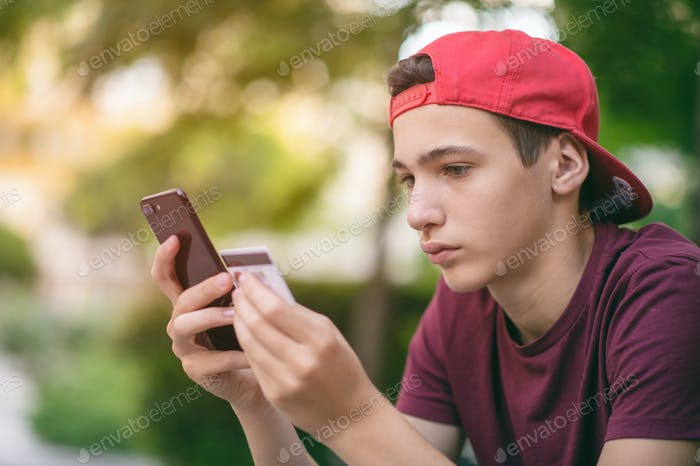 Teenage boy with a credit card and phone, outdoors.