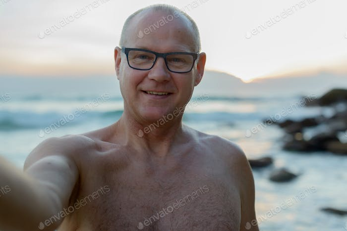 Mature handsome tourist man shirtless at the beach