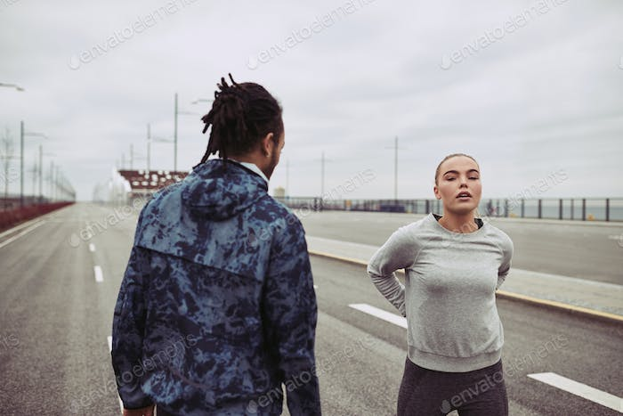 Young couple resting while out running together on a road
