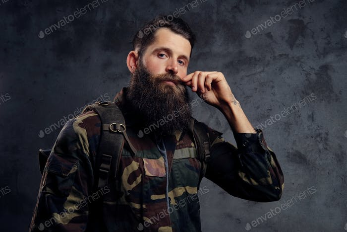 Handsome bearded traveler, dressed in a trendy camouflage jacket, standing in a studio