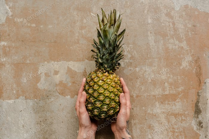 Cropped View of Woman Holding Ripe Pineapple on Weathered Surface