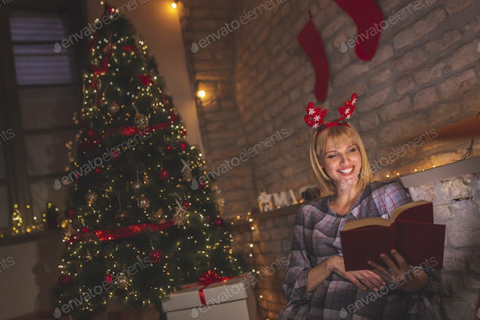 Woman reading a book on Christmas Eve