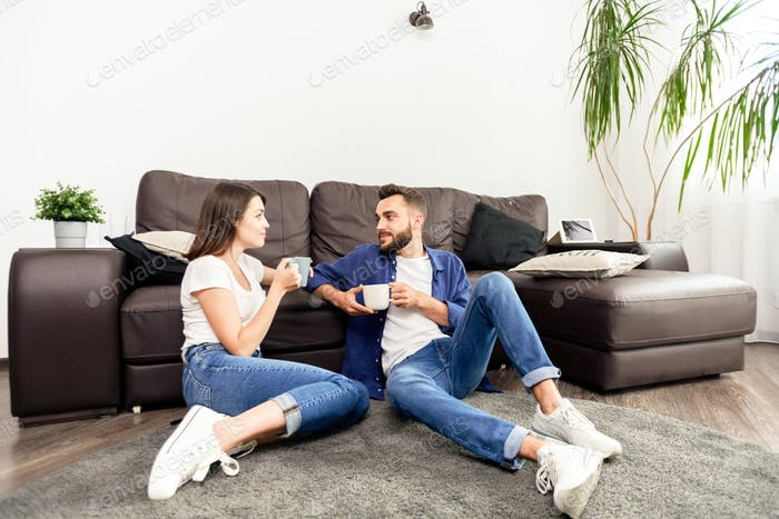 Content young couple in jeans and white shoes sitting on carpet