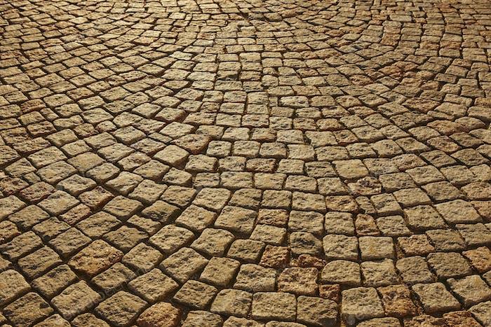 Street paving stone in warm tone. Antique urban sidewalk. Horizontal