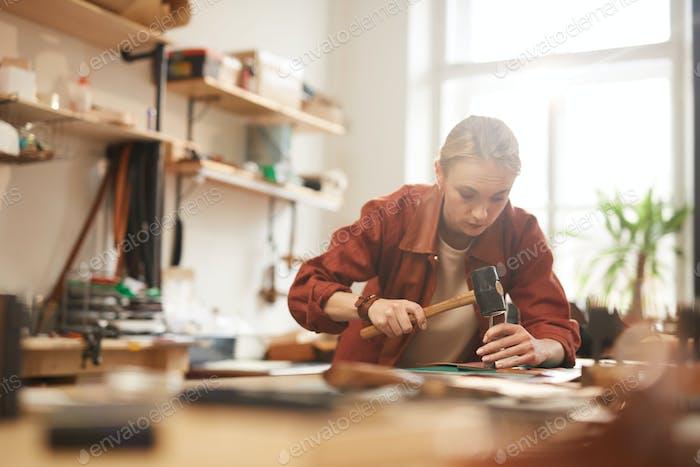 Artisan Using Hammer For Leatherwork