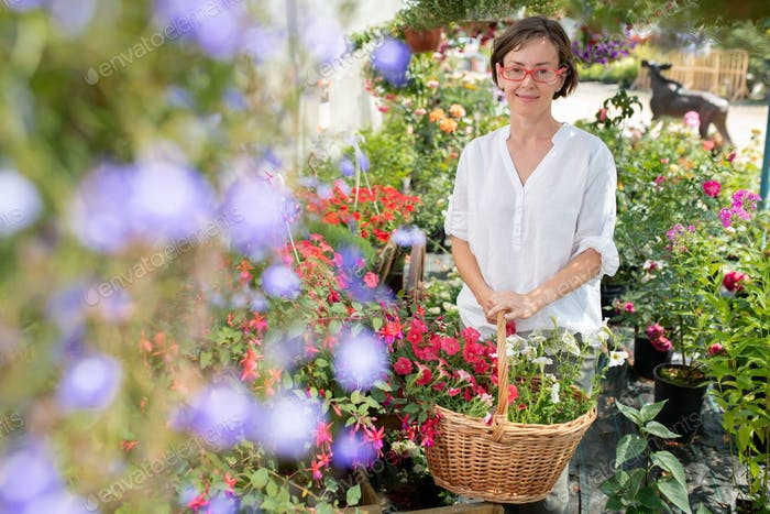 Pretty brunette female gardener with basket of flowers looking at you