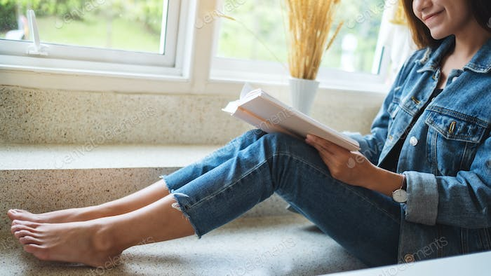 Closeup image of a beautiful asian woman sitting and reading book at home