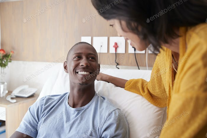 Wife Visiting And Talking With Patient Husband In Hospital Bed