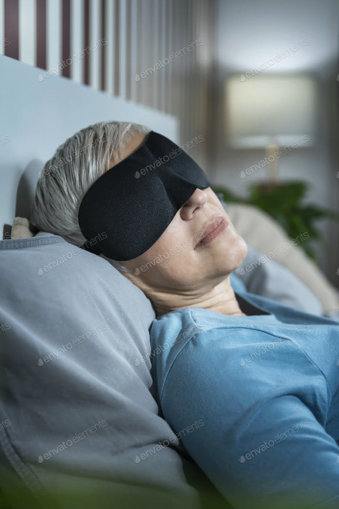 Mature Woman Wearing Black Sleep Mask, Lying in Bed