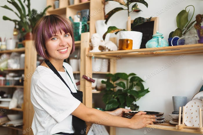 Smiling girl with colorful hair in black apron and white T-shirt putting handmade plates on shelf