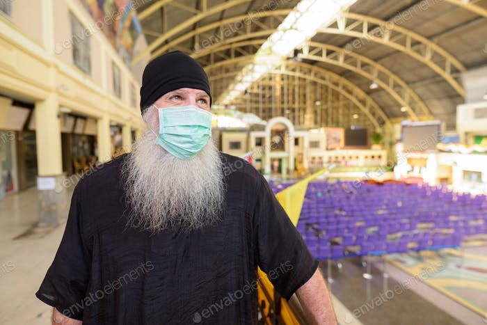 Mature bearded tourist man thinking with mask for protection from corona virus outbreak at railway