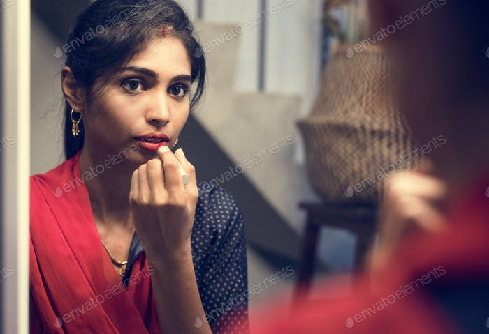 Indian woman putting on a lipstick
