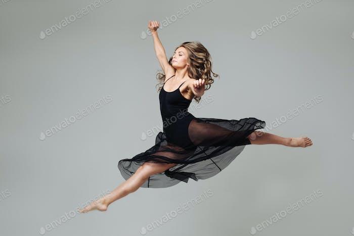 Balletttänzerin Frau schwarzes Kleid auf grauem Hintergrund.