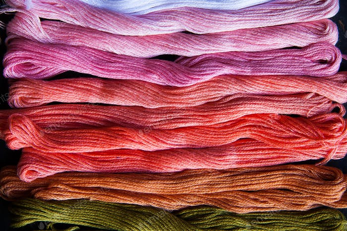 Skeins of multicolored embroidery threads on black wooden backgraund