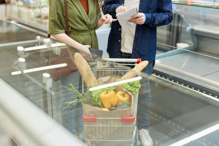 Couple Pushing Shopping Cart on Escalator