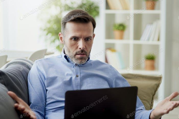 Hombre enojado que trabaja en casa en un ordenador
