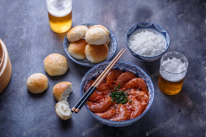 Prawns with tomato sauce, beer and buns, dark photo