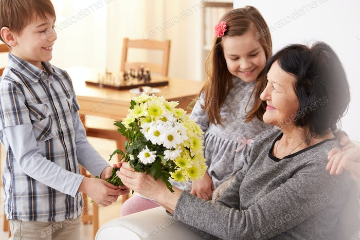 Grandchildren giving a bunch of flowers to their grandma