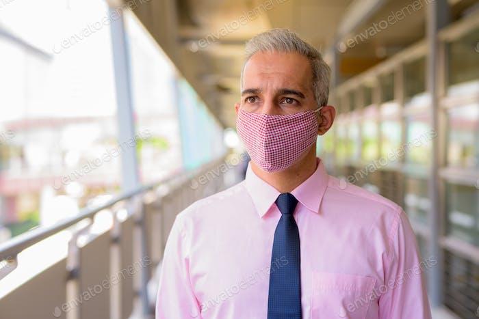 Gesicht des persischen Geschäftsmann mit Maske denken an der Fußgängerbrücke