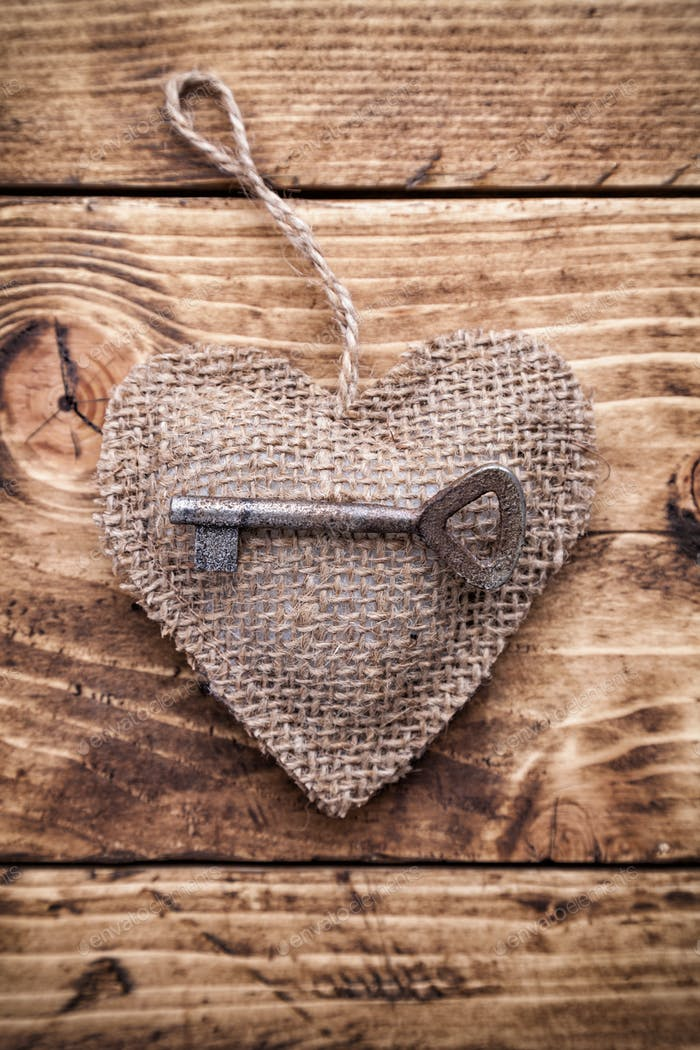Love concept. Old key and a heart on wooden background