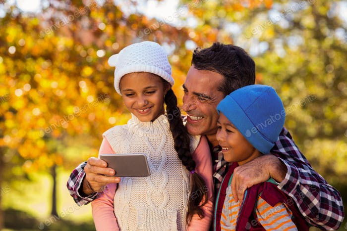 Happy father with children looking at mobile phone at park