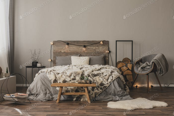 Copy space on empty grey wall of stylish bedroom interior with w