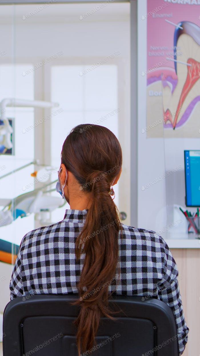 Zahnarzthelferin mit Schutzanzug und Zwischenablage