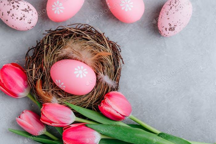 Buntes Osterei im Nest mit Tulpenblüten auf grauem Steinbetonhintergrund