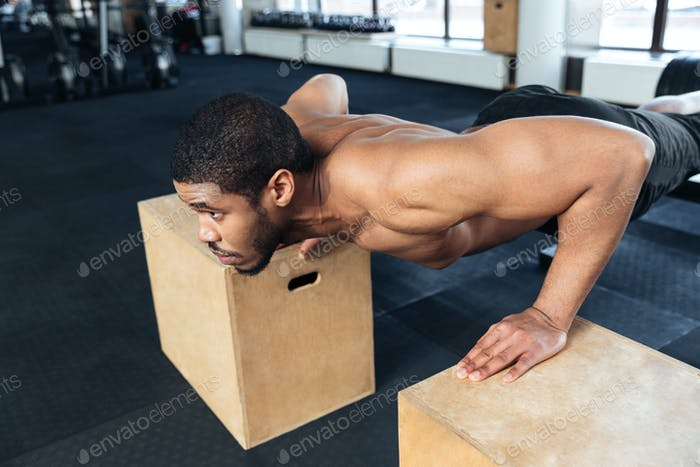Muscular fitness man doing push-ups in the gym
