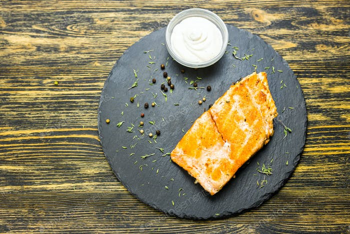 Grilled salmon steak with fresh lemon and sauce top view