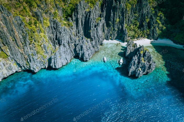 El Nido, Palawan, Philippines. Aerial above view of banca boats surrounded by karst scenery rocks at