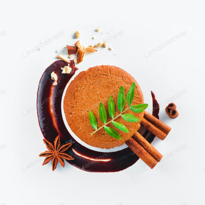 Cookie decorated with a chocolate swoosh, cinnamon, anise star and green leaves on a white