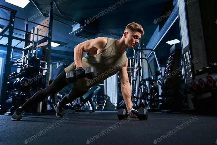 Hombre musculoso haciendo flexiones en una mano