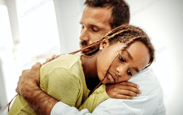 Doctor having conversation with sad little girl at the hospital. Doctor consoling child