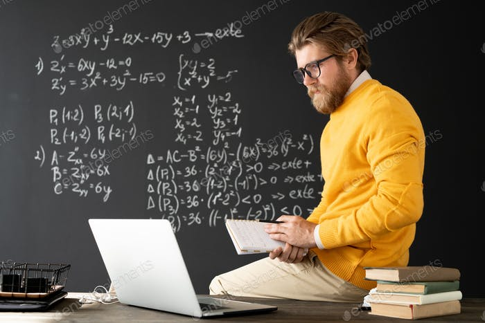 Young contemporary teacher with copybook sitting on table in front of laptop