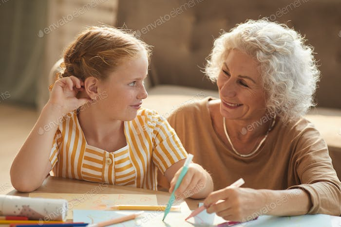 Happy Grandmother Drawing with Cute Girl