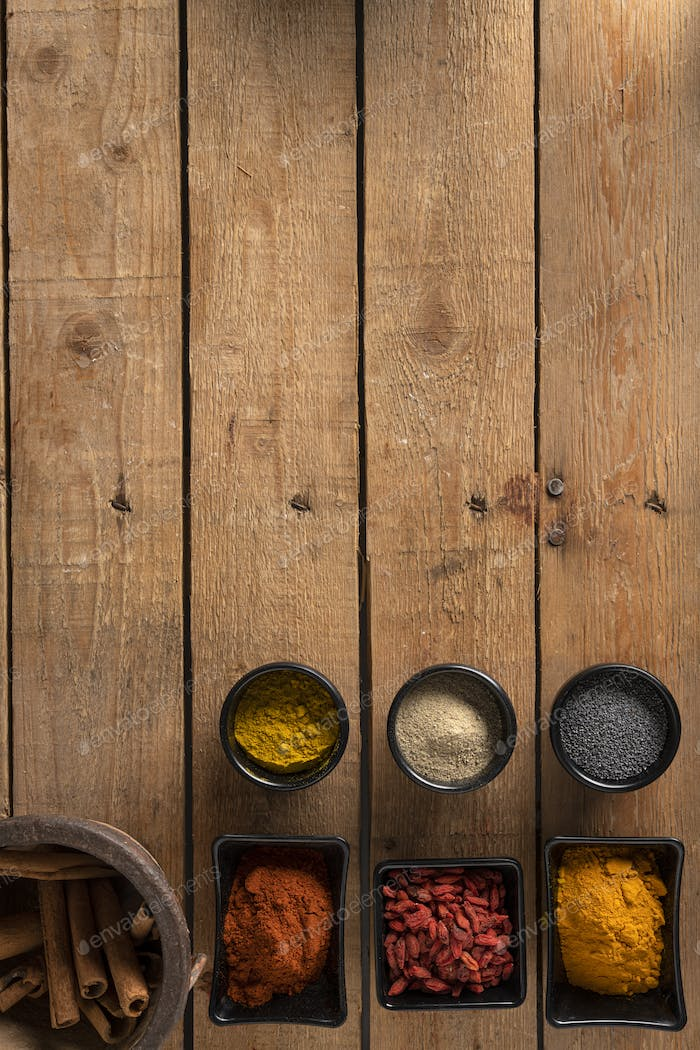 Bowls with spices on a wooden surface and a place for a logo