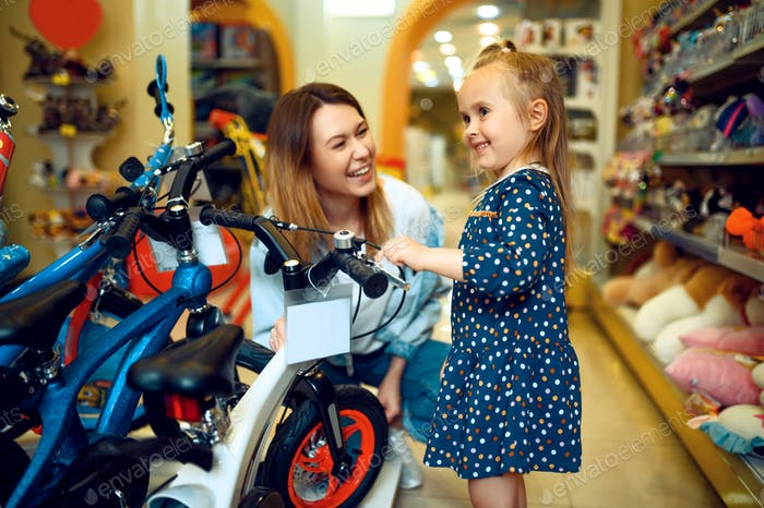 Mom and little girl choosing bicycle, kid's store