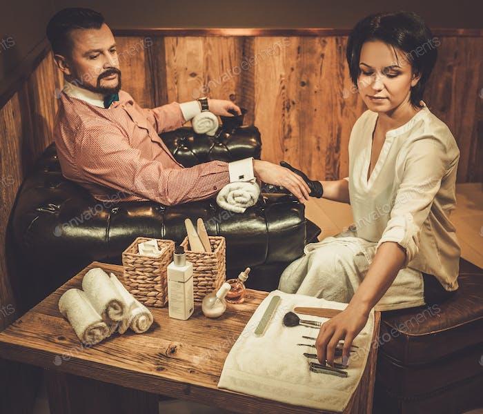 Уверенный старомодный мужчина делает мужской маникюр в парикмахерской.
