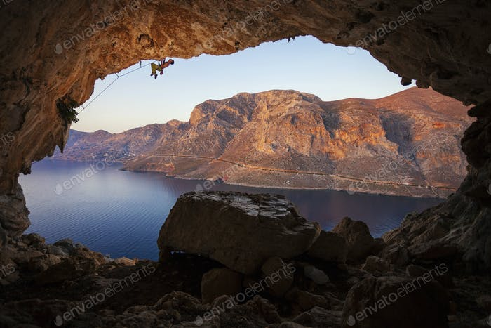 Male rock climber climbing along roof in cave before sunset.