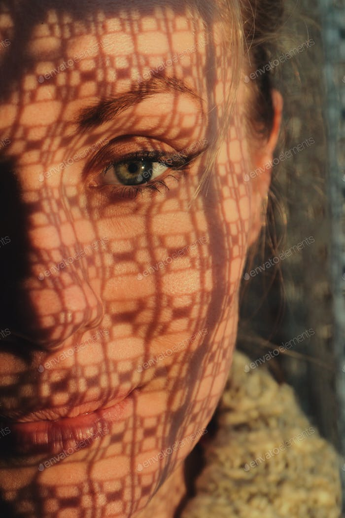 portrait of a woman standing next to a window, sunset through curtain cast a shadow on her face