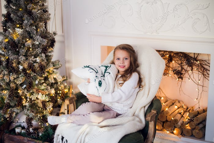 Little princess sit on armchair with deer pillow by Christmas tree at home