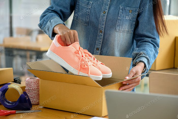 Online sellers are packing shoes in boxes to deliver to customers.