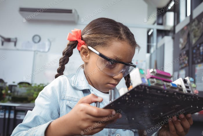 Concentrated elementary student examining circuit board