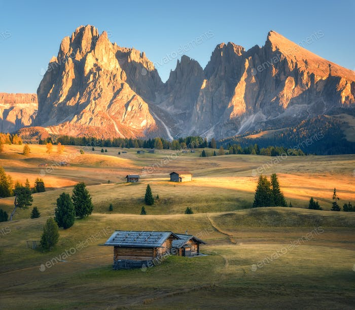 Small wooden houses in beautiful mountain valley at sunset