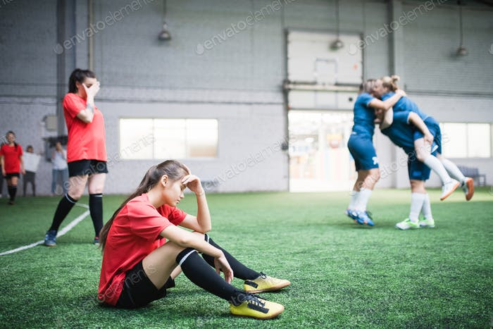 Tired young female football player and other girls resting after game