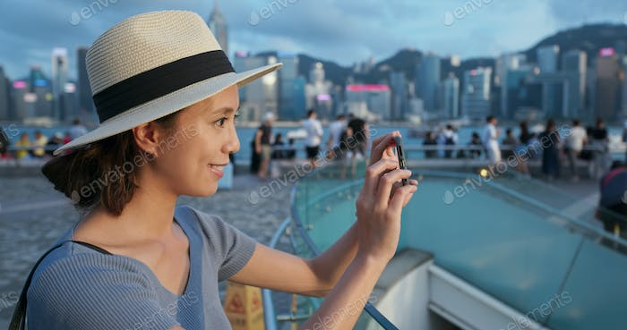 Woman use of mobile phone to take photo in city of Hong Kong